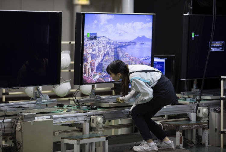 Работник проверяет телевизор на заводе Sharp в Яита в префектуре Точиги