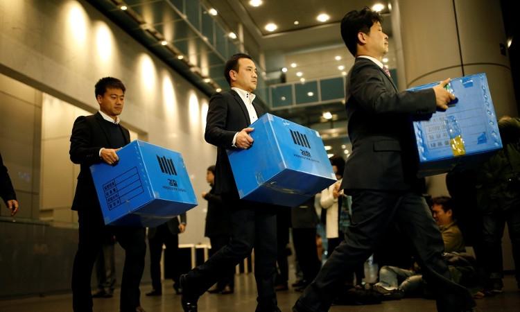 Следователи выносят вещественные доказательства из офиса Samsung