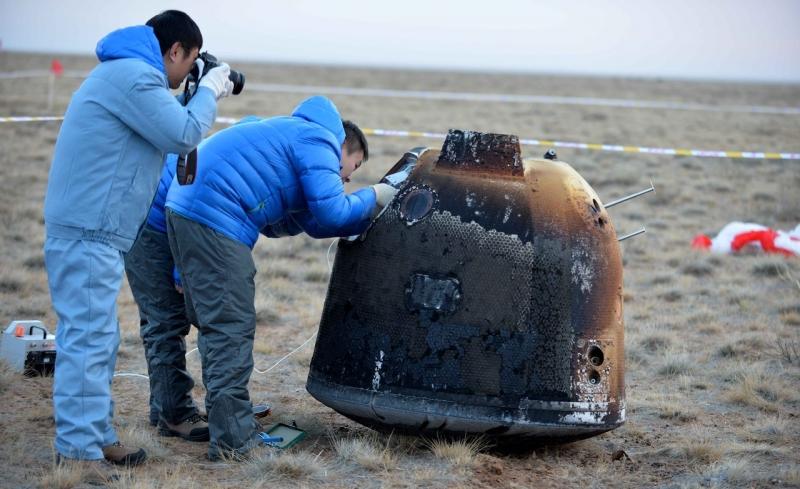 Специалисты группы поиска и спасания рассматривают спускаемый аппарат китайского зонда «Чанъэ-5-Т1», вернувшийся на Землю после облёта Луны. Фото CNSA.