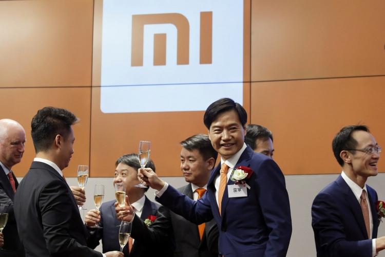 Второй справа — председатель и основатель Xiaomi Лей Юн (Lei Jun), во время дебюта акций его компании на гонконгской бирже (Bobby Yip / Reuters)