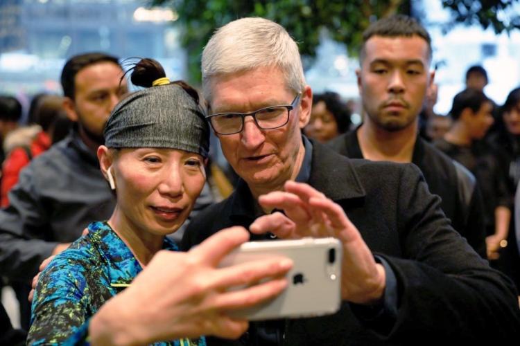 Тим Кук делает автопортрет вместе с пользователем iPhone во время визита в магазин Apple в Чикаго, 27 марта 2018 года, REUTERS/John Gress