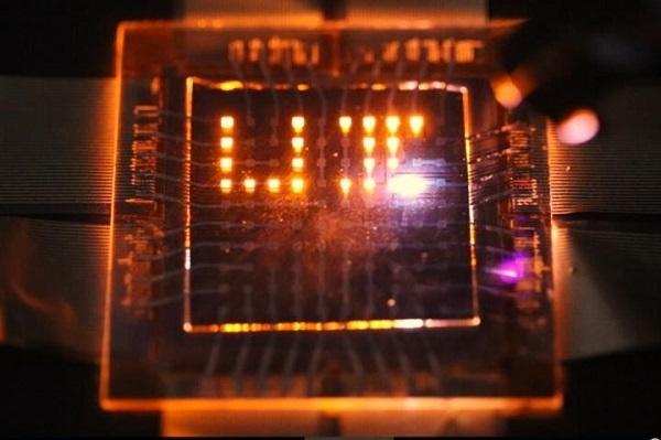 Лазерный луч выписывает литеры UI, символизирующие Иллинойский университет, на крупной сетке из пикселов с квантовыми наностержнями, которые в ответ на облучение светятся красным. Credit: Moonsub Shim, University of Illinois