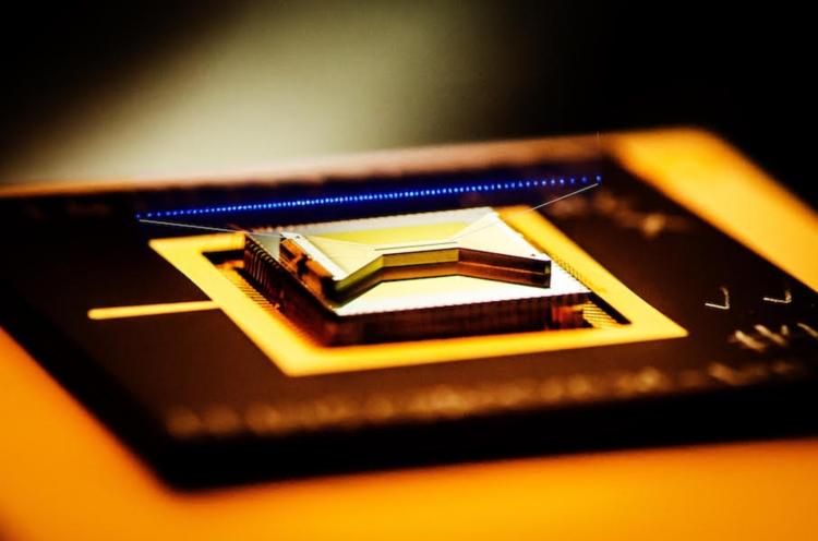 Квантовый чип от IonQ с наложенным изображением ионов