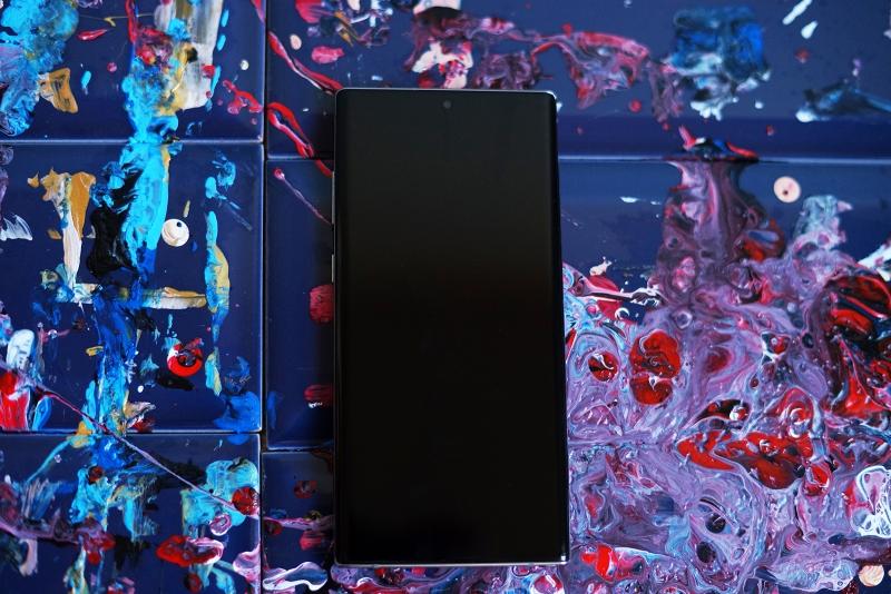 Samsung Galaxy Note10+, лицевая панель: дисплей с врезанной прямо в него фронтальной камерой; в нижней части в панель экрана спрятан сканер отпечатков. Под верхнюю грань почти незаметно вписана тоненькая прорезь разговорного динамика