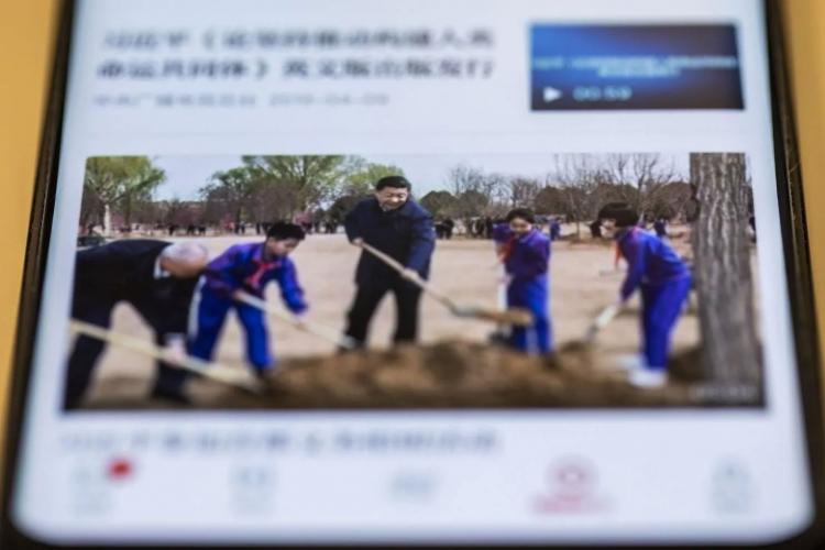 Си Цзиньпин сажает дерево — фотография из приложения «Изучение Великой нации» (Justin Chin/Bloomberg News)