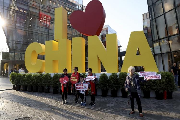 Люди с патриотическими надписями «Улыбки для Китая» и «Моя китайская мечта» рядом с инсталляцией «Я люблю Китай» в Пекине (Ng Han Guan/AP)
