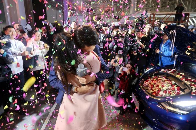 Сотрудник Tesla предлагает своей невесте произведённый в Китае автомобиль Tesla Model 3, наполненный цветами, на церемонии вручения на шанхайской фабрике (Reuters / Yilei Sun)