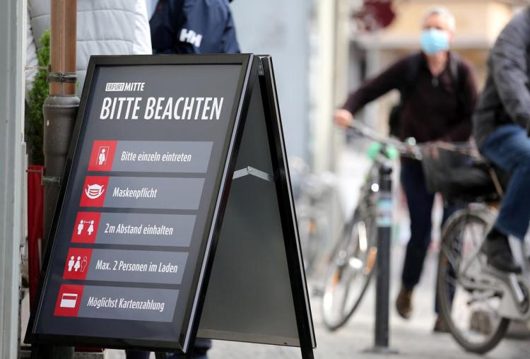 Знак у входа в магазин с правилами дистанцирования и уведомлением, что необходимо надевать маски. Эрфурт, Германия, 24 апреля 2020 года. REUTERS/Карина Хессланд