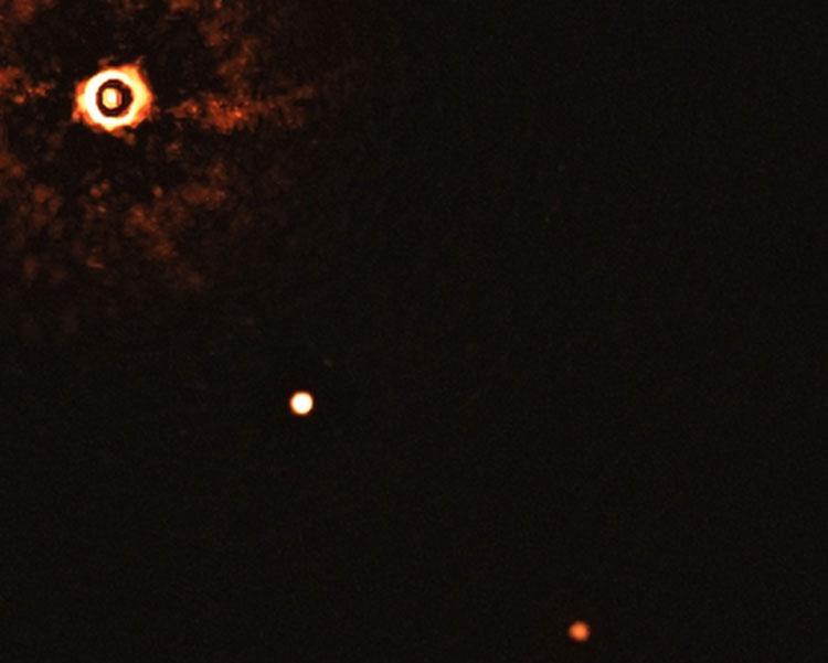 Снимок далёкой звезды (слева в верхнем углу, корона специально закрыта чёрным кольцом) и двух экзопланет на её орбите (ESO/Bohn)