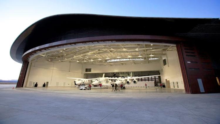 Космический корабль VSS Unity, пристыкованный к самолёту-носителю VMS Eve в ангаре космопорта «Америка» в Нью-Мексико