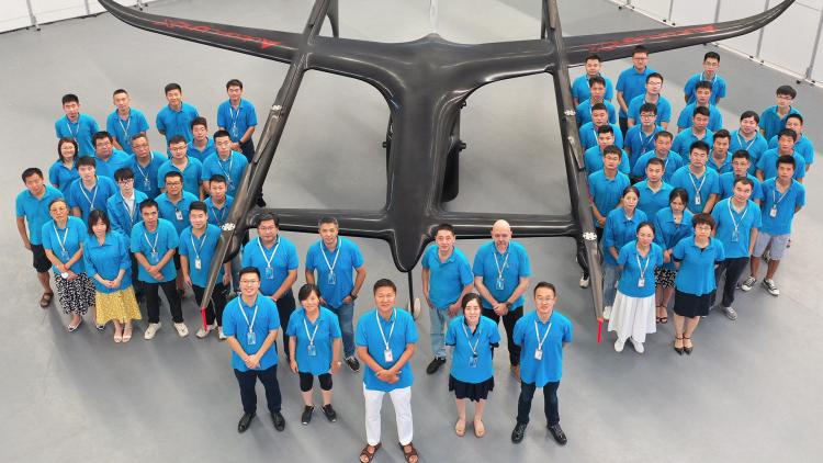 Часть команды Autoflight с основатлелем Тяном Юем (Tian Yu) в центр у прототипа грузового дрона V1000 eVTOL — он определённо тяжелее и больше V400