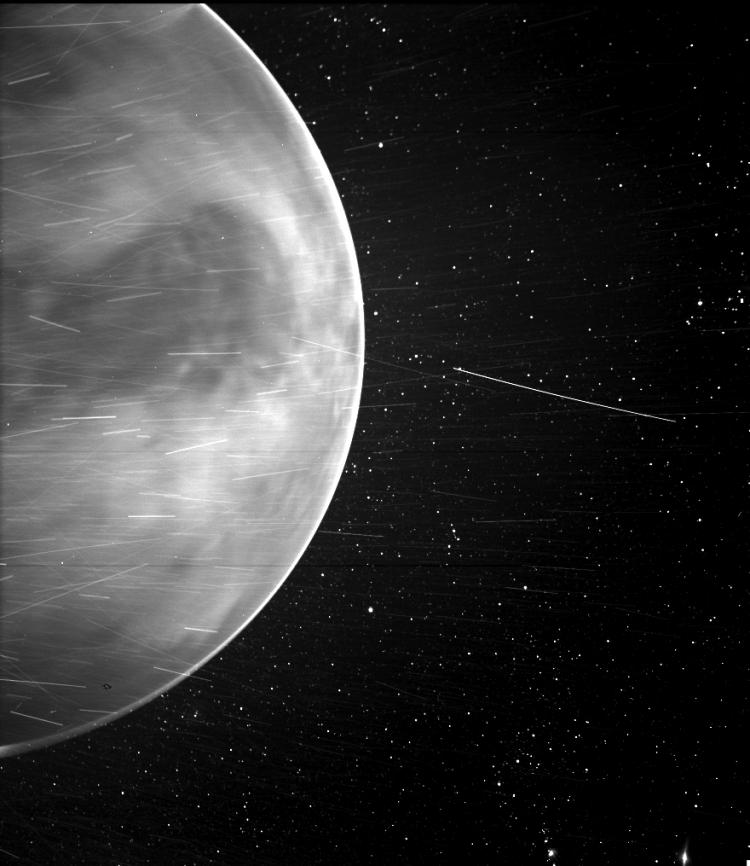 Чёрно-белое изображение, показывающее одно полушарие Венеры на фоне звёзд, с яркими полосами