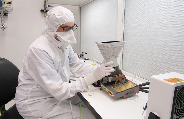 Инженер (APL) устанавливает на тестовую модель системы визуализации детекторную электронику широкоугольной камеры (NASA/APL/Ed Whitman)