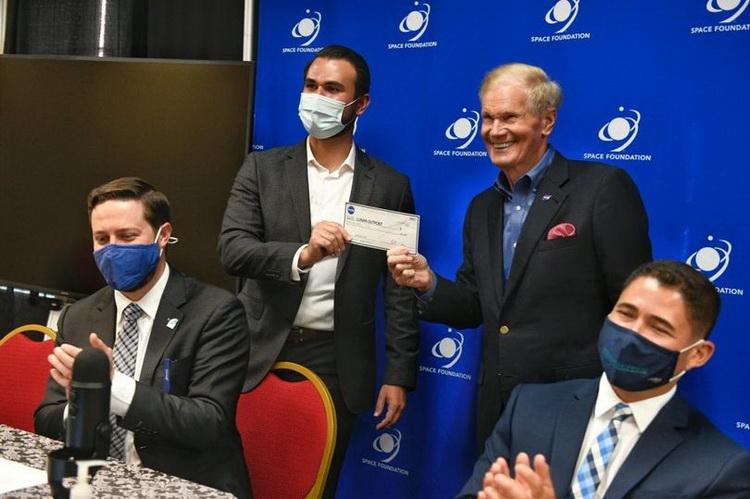 Глава NASA Билл Нельсон передаёт чек на 10 центов главе Lunar Outpost Джастину Сайрусу (Фото: Space Foundation)
